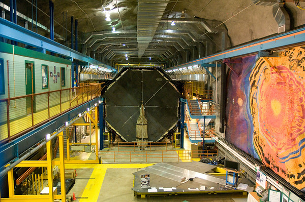 The MINOS Far Detector, buried 2,341 feet beneath the earth in the Soudan Mine in northern Minnesota. A mural by Joseph Giannetti about the power of science is painted on the right wall.